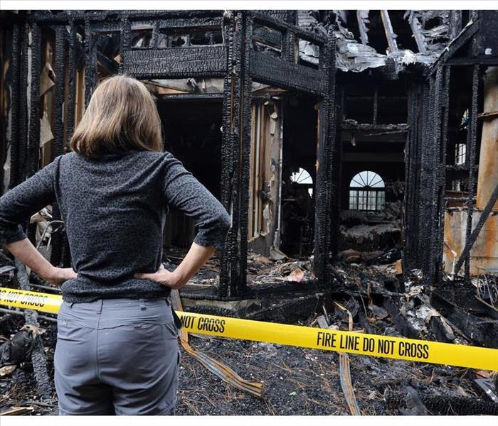 A woman standing by a security fence of a building that is damaged by fire