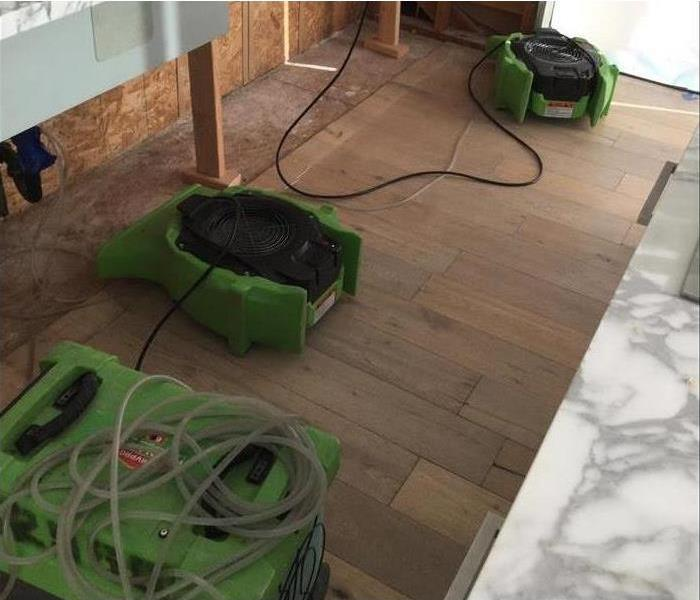 Air movers drying kitchen floor